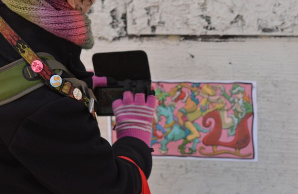 a woman in pink gloves is taking a picture of a graffiti paste up in a street, taking the photo with her phone