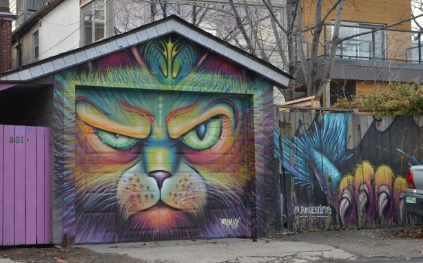 shalak and clandestinos painting of a colourful cat face and paw with claws, on a garage door and fence in a lane