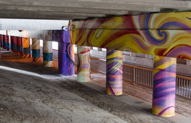 pillars and supports under an overpass that have been painted in bright colours by smoky and shalak - swirls of purples and yellows
