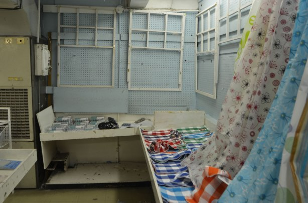 interior of Honest Eds store as it gets ready to close down. a few shower curtains on display as well as some checkered tea towels. The rest of the shelves and wall space are empty