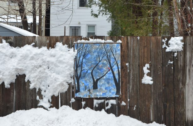 small amateur paintings displayed on a wood fence, with trees and houses in the background, snowy day, a black tree on a blue background. Snow has been blown against the wood fence and some of it has stuck to the fence, Craven Road