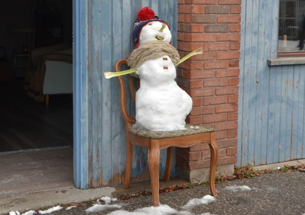 a little snowman stands on a chair outside. A red cap, celery for arms, avocado for mouth
