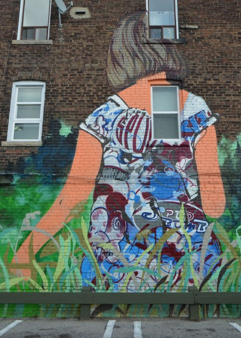 part of a larger mural, a young woman with her back to the viewer, walking through long grass