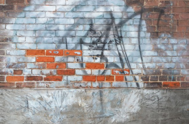 a wall. Upper part is brick. A swath has been painted white, but some bricks have broken off in front to reveal the brighter orangish red underneath. The bottom part of the wall is grey concrete that has been texturized with slanted lines.