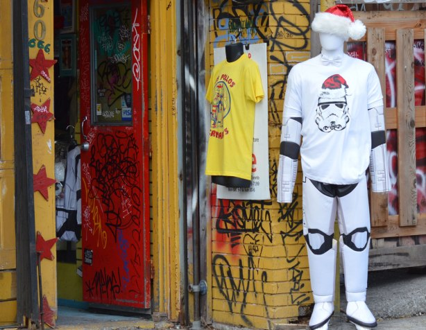 a mannequin outside a store is dressed in a Star Wars white storm trooper costume with a Santa hat and a T-shirt with the face of a stormtrooper also with a Santa hat. The store is painted yellow and has a bright red door that is open
