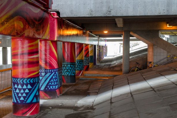 pillars and supports under an overpass that have been painted in bright colours by smoky and shalak - red pillars with blue geometric patterns in a band around it near the bottom