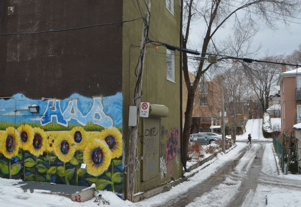 looking down a lane. A mural on a wall is on the left. It is bright yellow sunflowers under a blue sky. Snow in the alley with car tracks from a few vehicles, trees, a house, osme garages,