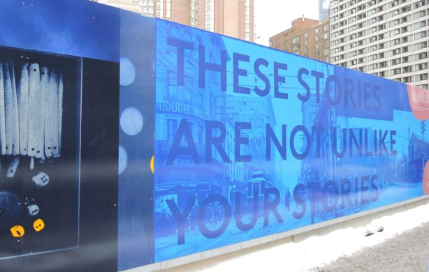 part of a larger mural in Toronto, blue photos, with words written in large capital letters, These Stories Are Not Unlike Your Stories