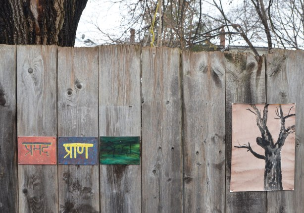 small amateur paintings displayed on a wood fence, with trees and houses in the background, snowy day, four paintings. One black tree on light brown paper, and three small paintings with words in a different language with a different alphabet, Bengali perhaps