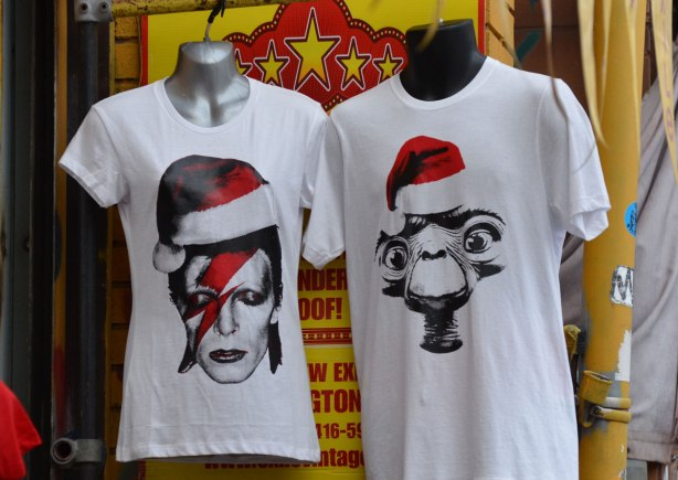 two t-shirts on display outside a store, both are white and both have heads of famous people wearing Santa hats. One is David Bowie and the other is E.T.