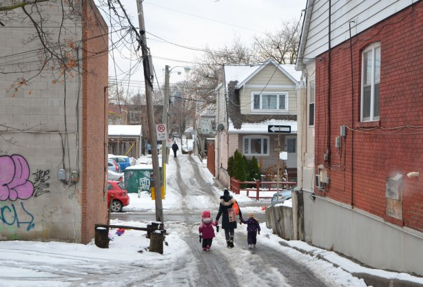 A woman walks her two young children home from school, down a snowy lane, one on each hand. Their back is to the camera, houses, trees, hydro ples, a car on the street they are about to cross.