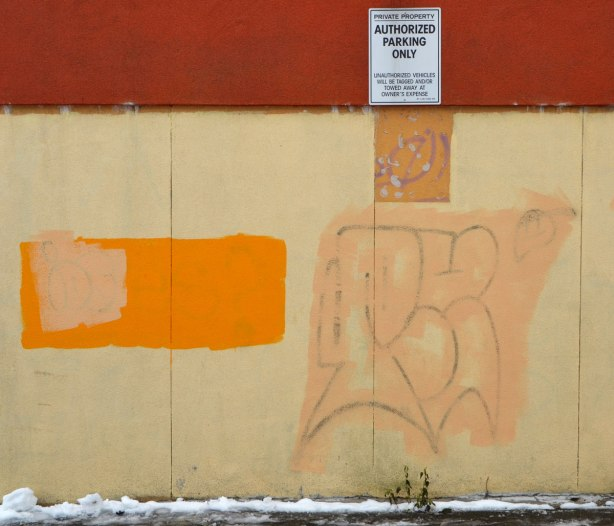 Yellow wall with rust coloured upper part. Tags and graffiti have been painted over with different colours of yellow paint to produce a patchwork like effect.