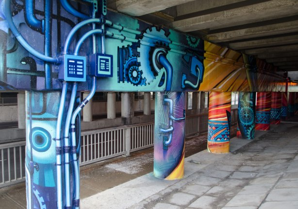 pillars and supports under an overpass that have been painted in bright colours by smoky and shalak