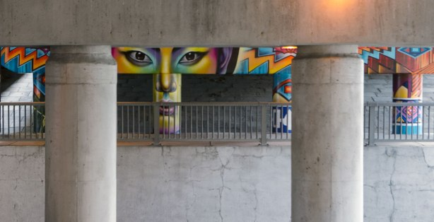 looking across Wilson Avenue, under the Allen Expressway towards a mural that has been painted on the pillars and supports on the other side. A face is painted there.