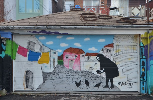 mural on a garage door of a woman feeding some chickens in a yard with colourful laundry hanging out to dry, houses in the background, mural on a garage door.