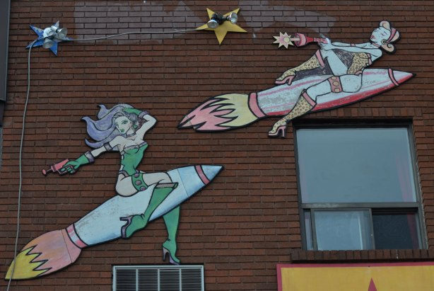 wooden decorations on the upper part of a store, cutouts painted to look like two women sitting on top of rockets as they blast into space