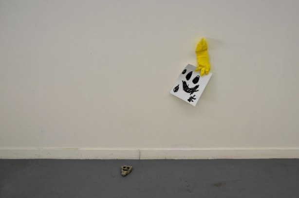 a black happy face scrawled on a piece of paper, a yellow rubber gloved taped to the wall that is holding the paper. A small rock on the floor with a happy face painted on it.