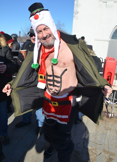 people participating in the 12th annual polar bear dip at Sunnyside Park in Toronto, in the icy cold water of Lake Ontario - a swimmer with a Santa outfit sort of, apron and tie