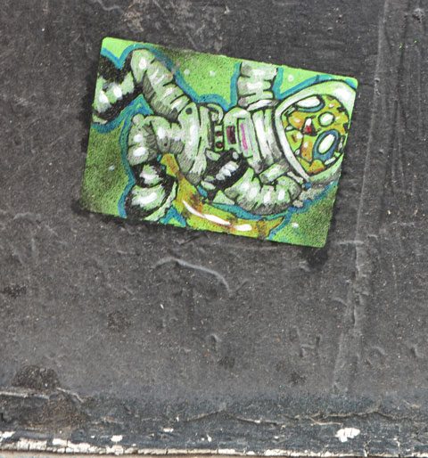 a small paste up of an astronaut floating in space, on a black wall, close to the ground.