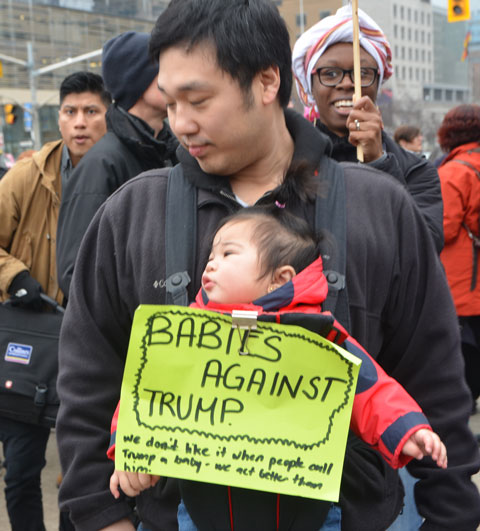 a man carries a baby in front of him, with a yellow sign that says Babies against trump, marching in the Womens March in Toronto with other men and women.