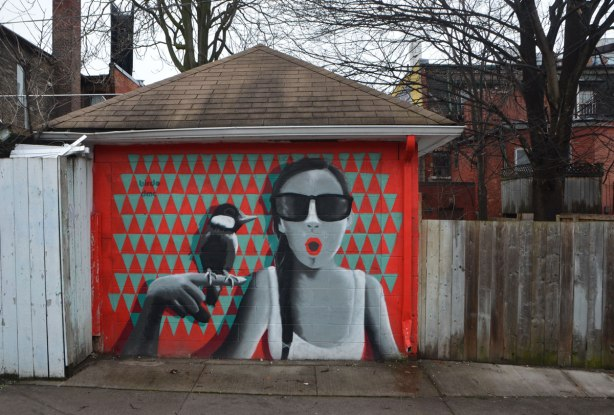 a birdo mural on a garage door of a woman in grey tones with a round red mouth in the shape of an O. she is holding her hand up near her face and a bird is sitting on it. The background of the mural is red and greenish triangles.