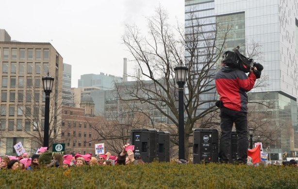camera man stands on a high level of ground along with some large black speakers. The heads of some women can be seen , all wearing pink hats for the Womens March