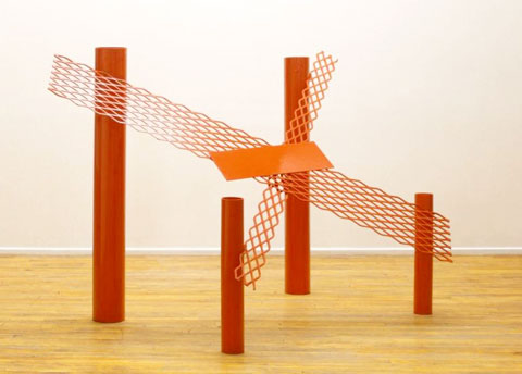 red sculpture by anthony caro, metal, 4 upright cylindrical tubes with metal mesh forming an X on top of them.
