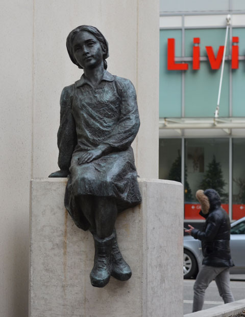 sculpture, Two Children of Toronto by Ken Lum in a downtownwalkway with a concrete bulding beside it, looking towards the girl, with Bay Street and Canadian Tire store behind