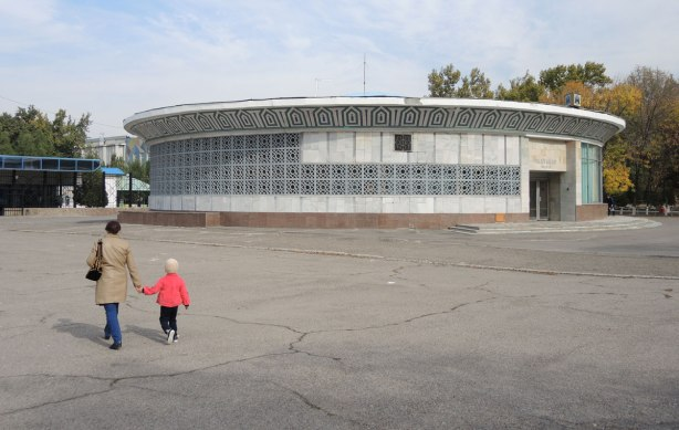 a mother and child walk towards a low circular building which is a metro entrance, part of the Tashkent subway system. It is surraounded by pavement. There are no other people in the picture