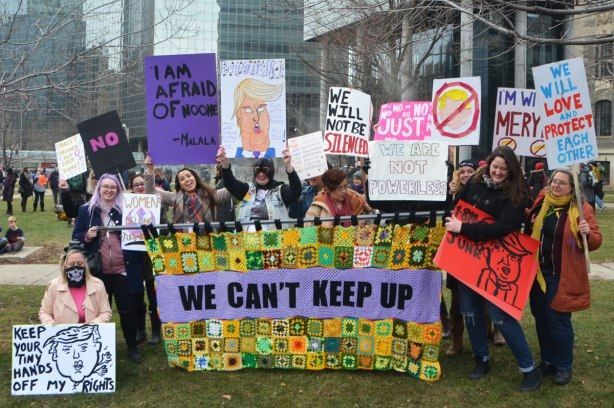 a group of women carrying a banner that has been made of many crocheted granny squares and the words we can't keep up. womens march in Toronto, waiting at Queens Park for the march to begin.
