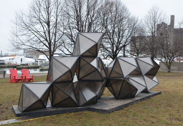 public art installation in a park along Lake Ontario, diamond shapes stacked in a pile, 10 pieces altogether, 5 on the bottom, 4 on the next row and one on top, grey in colour, bare trees and boats covered for the winter are in the background.