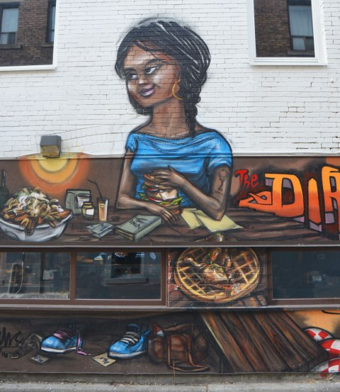 from a mural by elicser along the exterior wall of the dirty bird chicken and waffle restaurant - a woman is sitting at a table in the restaurant