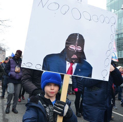 a young boy in a blue hat carries a placard that he's made that says Noooooo and has a picture of Donald Trump with a black Darth Vader mask on.
