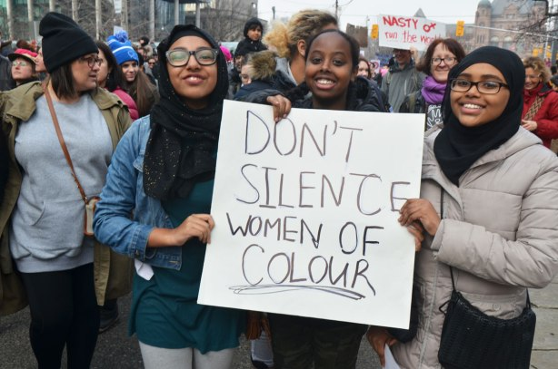 Three black women, one with a head scarf on, hold a sign that says Don't silence women of colour, part of a crowd at Womens March, toronto
