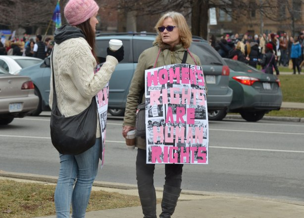 two women stand on the sidewalk, one is drinking coffee and wearing a pink hat. The other is holding a sign that says womens rights are human rights in pink letters ona background of black and white photos.