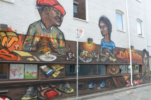 from a mural by elicser along the exterior wall of the dirty bird chicken and waffle restaurant - a woman and a man are sitting at a table in the restaurant eating chicken and waffle sandwiches