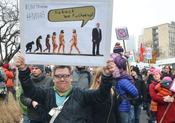 Womens March, toronto - a man holds up a sign that is a play on the evolution of man meme, as they walk upright they come to a figure of Donald Trump. The last man in the evolution chain turns around and says Go back, we fucked up.