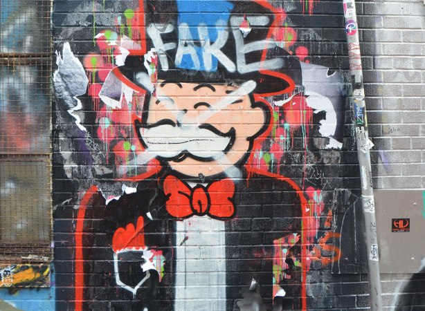 the man from the monopoly game is painted on a wall. Someone has sprayed a white x through his face and written the word fake on his top hat.