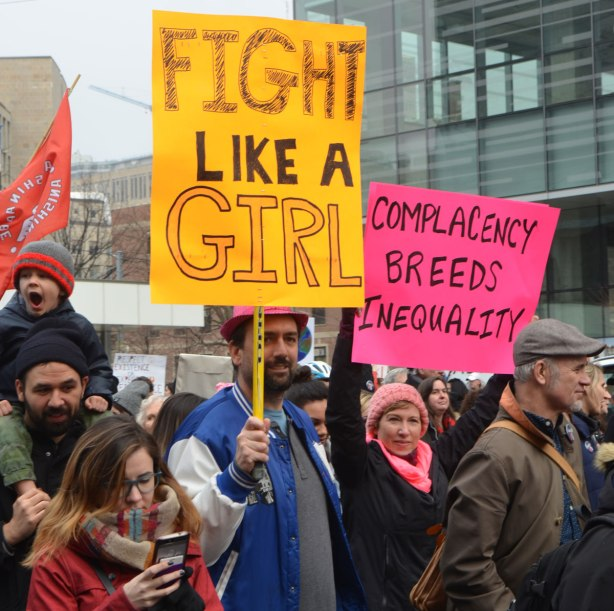 a man holds a sign that says Fight like a girl. and a woman beside him the march holds a sign that says complacency breeds inequality.