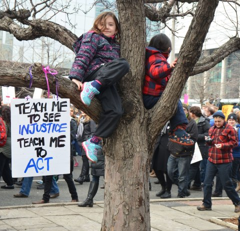 a young girl in a purple jacket is sitting on the branch of a tree. Her sign is strung over the branch and it says Teach me to see injustice teach me to act. People in the Womens March, toronto are walking past her in the background.