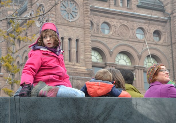 a young girl in pink sits on top of the War Memorial at QUeens Park, the parliament buildings are behind her.
