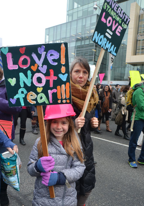 a young girl carried a brightly painted sign that says Love not fear. She is walking with her mother in the Womens March on University Ave. She is also wearing a pink hard hat.