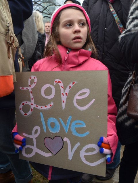 a young girl in pink holds a sign that says love love love. Womens March, toronto