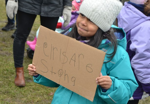 a young girl holds a sign that says girls are strong. She's written it herself on cardboard.