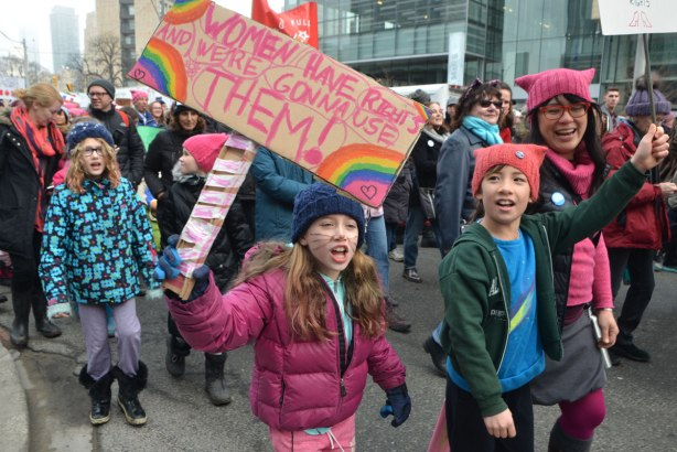 a girl in pink is holding a sign that says WOmen have rights and we're gonna use them. She is shouting as she marches, Womens March, toronto . There are other kids with her
