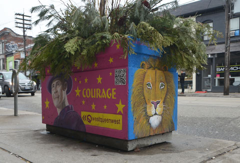a rectangular cement planter on Queen Street west with pine and cedar boughs in it. The sides have been painted. On the end is the head of a lion, on the side is the word courage and a picture of Gord Downie from the music group The Tragically Hip