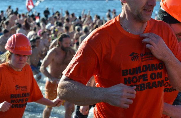 people participating in the 12th annual polar bear dip at Sunnyside Park in Toronto, in the icy cold water of Lake Ontario - Habitat for Humanity team wore orange T shirts and orange hard hats