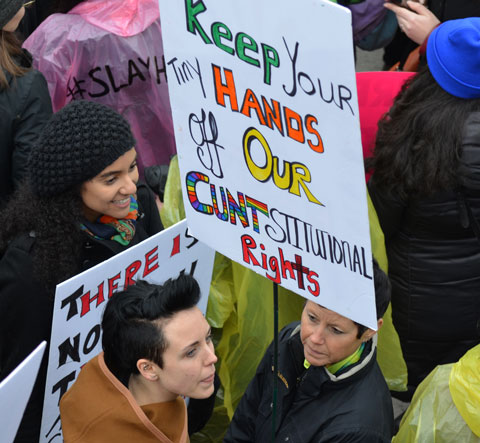 a woman stands in a crowd at NathanPhillips Square, Womens March, toronto - she is holding a sign that says Keep your hands off our cuntstiutional rights.