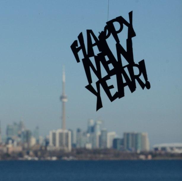 a happpy new year sign hangs from the ceiling in a window, the view from the window is in the background, the Toronto skyline with the CN Tower and Lake Ontario