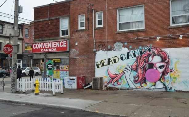 on the corner of Queen West and a smaller side street, the Convenience Canada store with a small white picket fence outside of it. On the wall is a mural of a woman blowing a big pink bubble with gum and the words head candy written above her head.